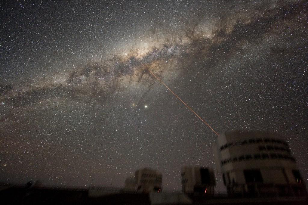 """Skrendam ten? Ne, iš tikro tai ten mes neskrendam – Saulė juda aplink Galaktikos centrą, o ne jo link. Čia matomas spindulys yra """"dirbtinė žvaigždė"""" – lazeris, naudojamas teleskopuose kaip orientyras, leidžiantis įvertinti ir kompensuoti atmosferos sukeliamus tikrų žvaigždžių vaizdo iškraipymus. ©ESO"""